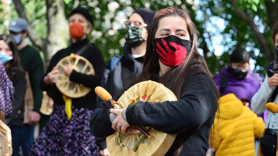 Une jeune femme avec un tambour et un masque.