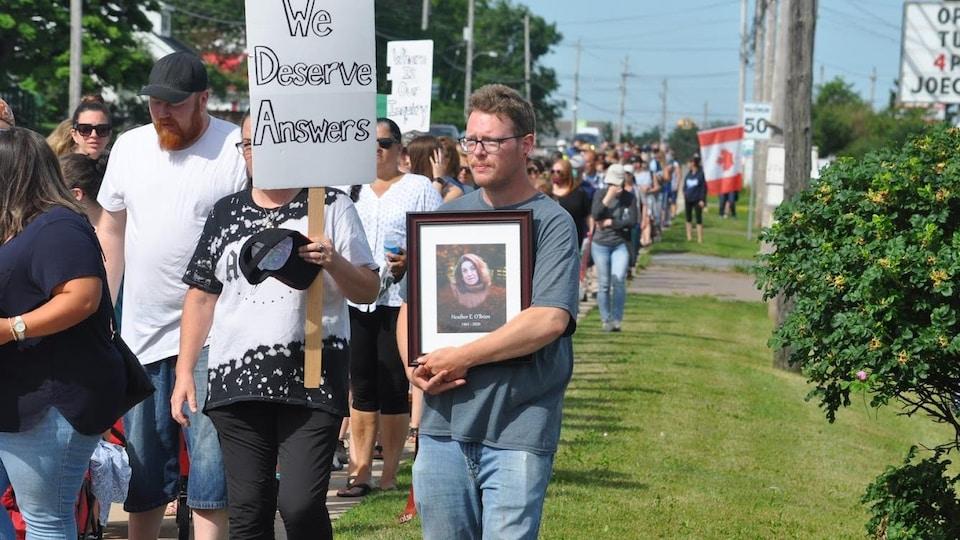 Des manifestants tiennent une affiche sur laquelle on peut lire : We Deserve Answers.