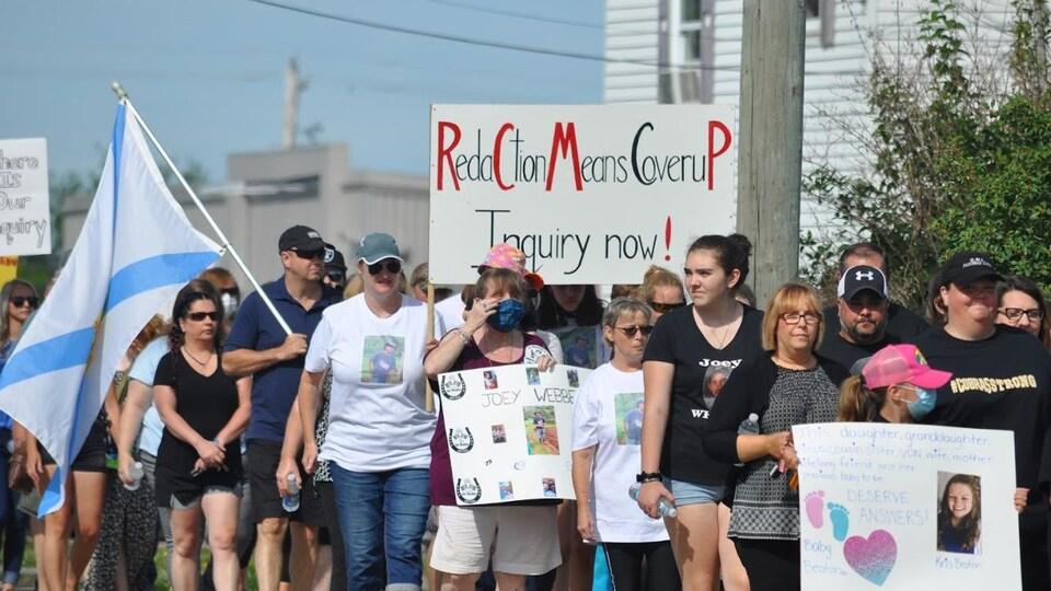Des manifestants tiennent une affiche sur laquelle on peut lire : RCMP Inquiry Now!