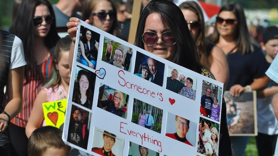 Des manifestants tiennent des affiches en mémoire des victimes de la tuerie.