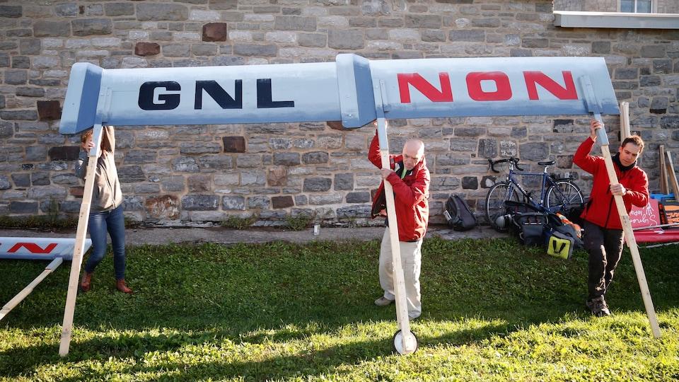 Trois personnes installent une grande pancarte sur laquelle est écrit GNL NON.