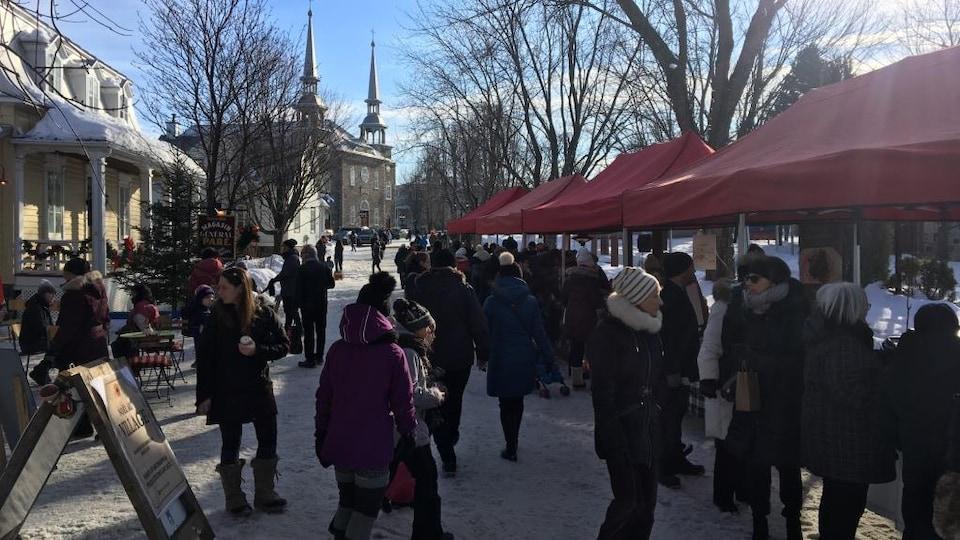 Dans un décor enneigé les gens se promènent de kiosque en kiosque.