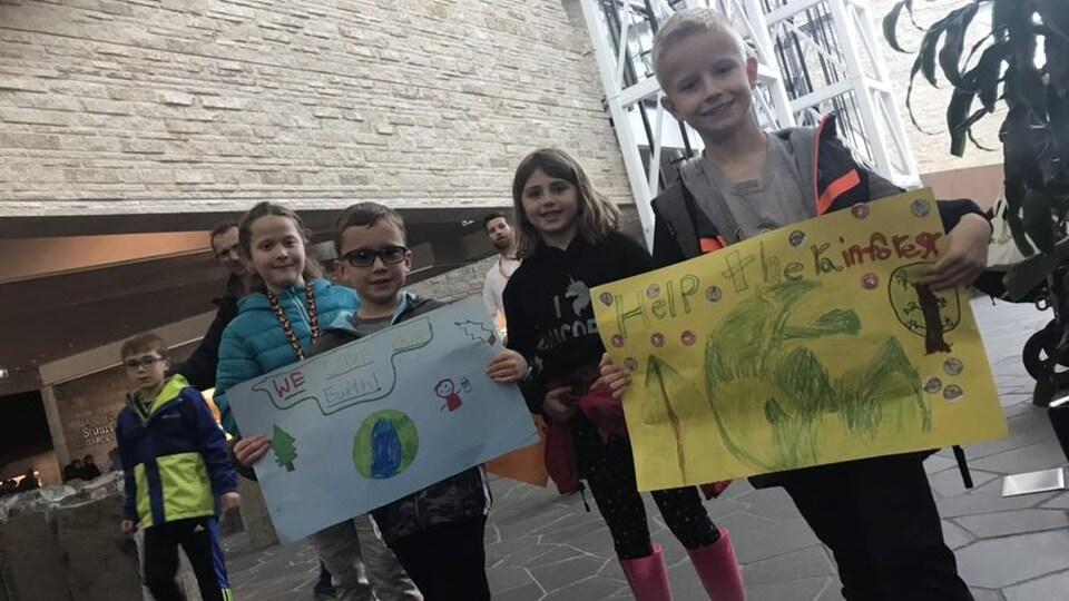 Des élèves qui tiennent des affiches faites à la main sourient à la caméra.