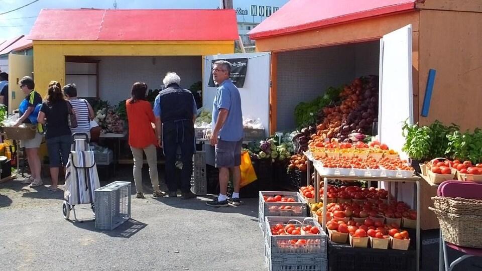 Des clients devant une table de légumes.