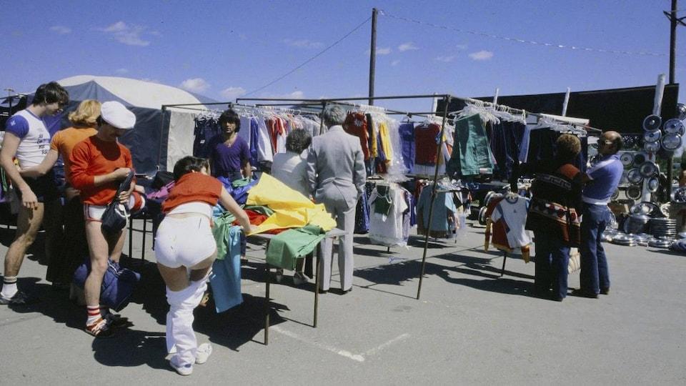 Clients devant un kiosque de vêtement au marché aux puces Saint-Hippolyte.