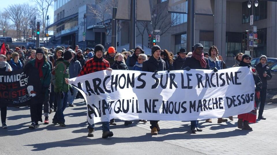 Les manifestants avec des affiches, dont une où il est inscrit: Marchons sur le racisme avant qu'il ne nous marche dessus
