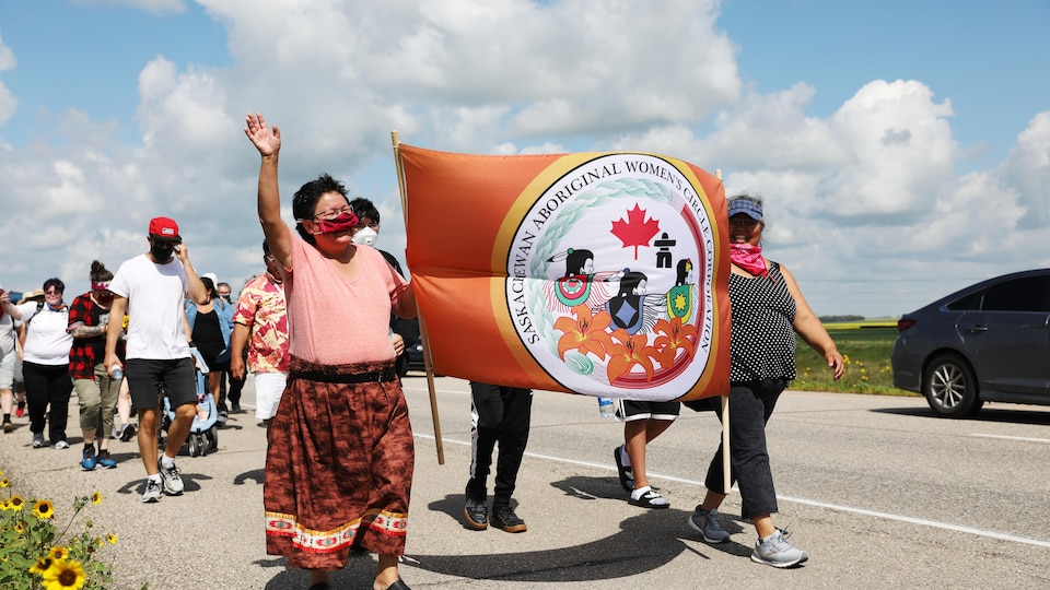 Des gens marchent sur l'autoroute en Saskatchewan. Ils participent à la marche Walking With Our Angels.
