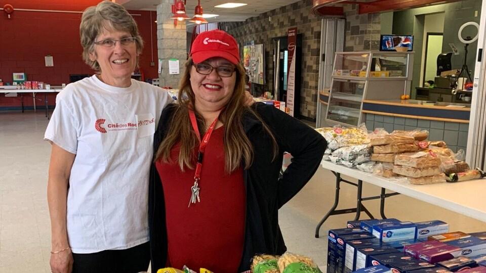 Deux femmes regardent la caméra en souriant. Autour d'elles on voit des tables sur lesquelles sont étalés des produits d'épicerie.