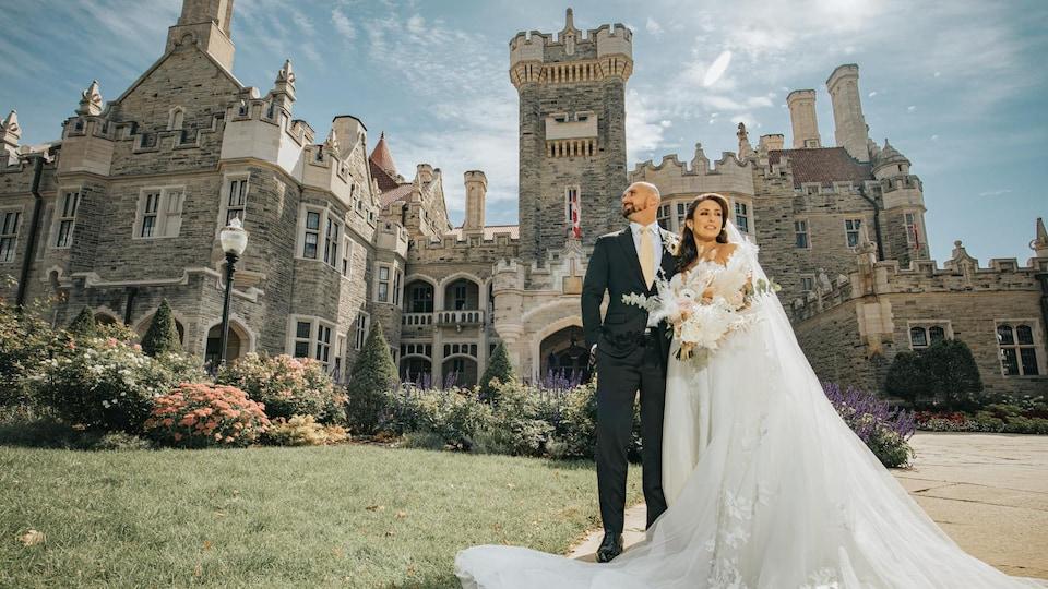 Maria Bhersafi et Marc Poirier, en tenue de cérémonie, devant un luxueux château.