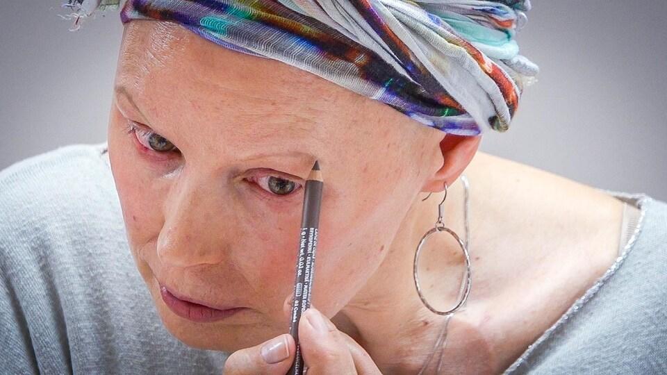 Une dame dessine son sourcil gauche devant un miroir avec un crayon de maquillage.