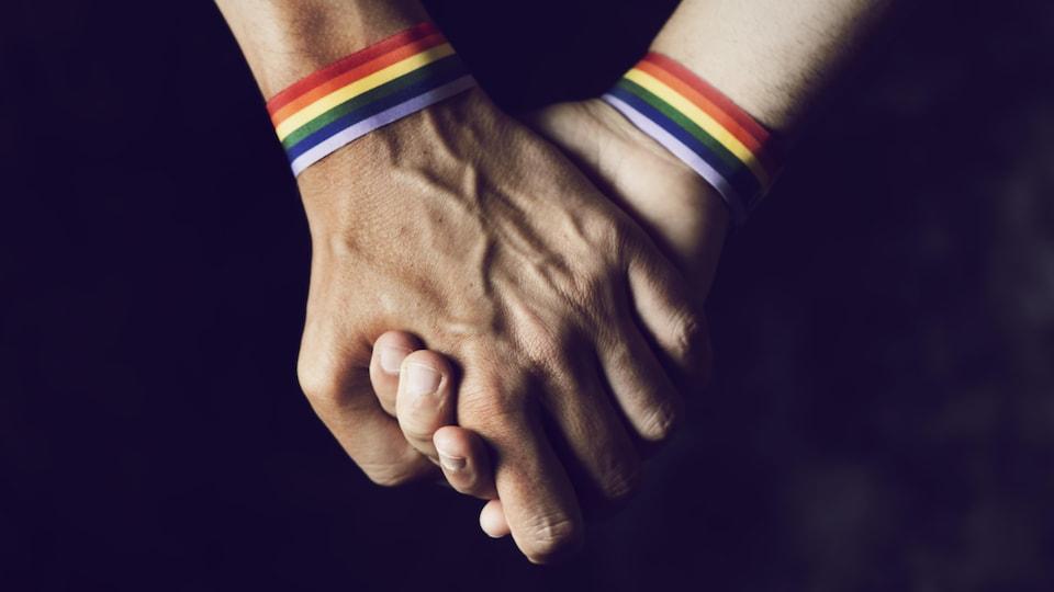 Deux mains serrées. Sur chacun des poignets, on voit un bracelet arc-en-ciel.