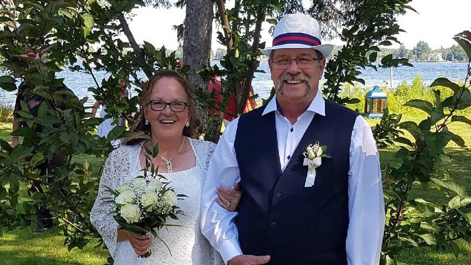 Une femme vêtue d'une robe blanche et tenant un bouquet de fleurs dans les mains aux côtés d'un homme qui porte un habit de couleur blanche et une veste bleue.