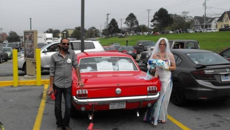 Le couple pose avec leur Mustang 1966.