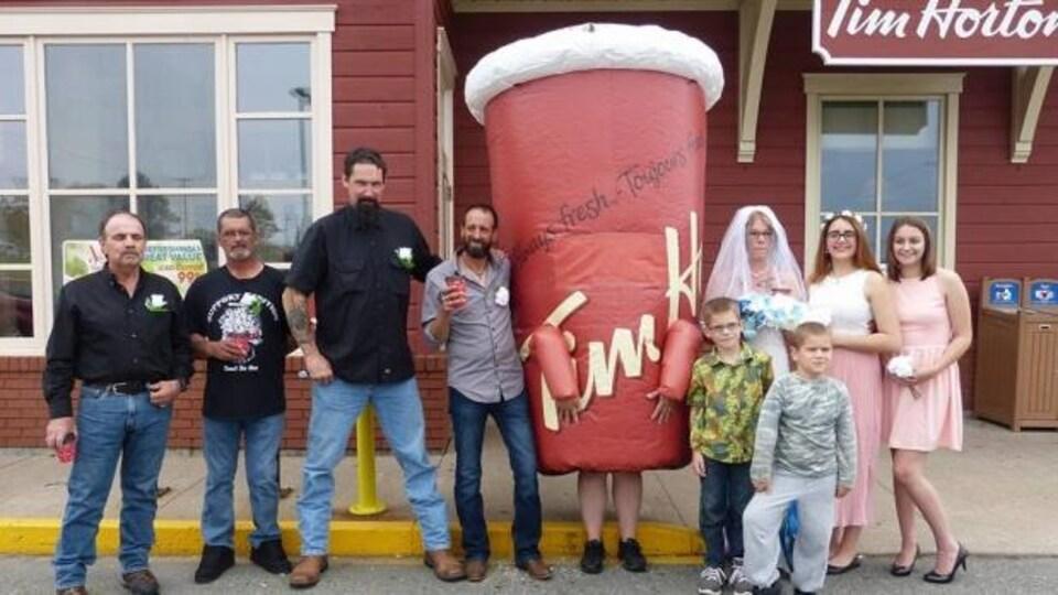 Photo de groupe avec la mascotte déguisée en tasse de café géante.