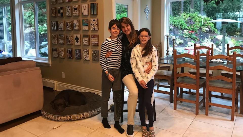 Une mère avec ses deux enfants, tous souriants, posant devant la table de cuisine de leur maison.