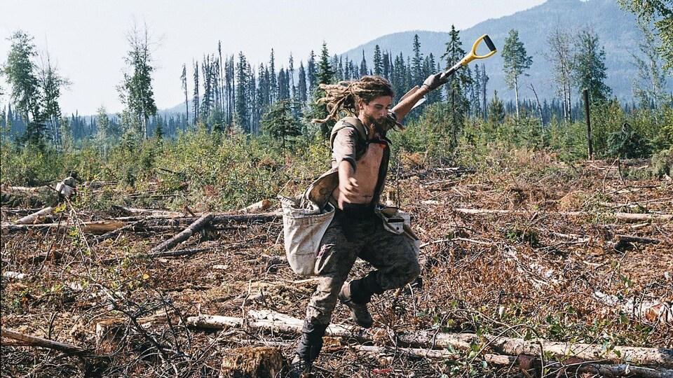 un homme habillée en tenue de chantier, une pelle à la main, replante des arbres.