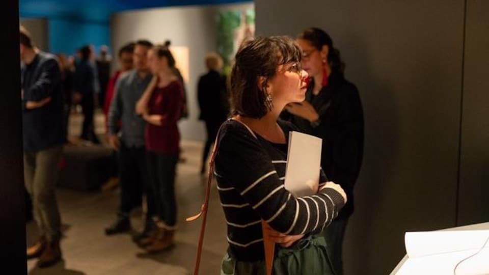Une femme regarde une toile dans un musée.