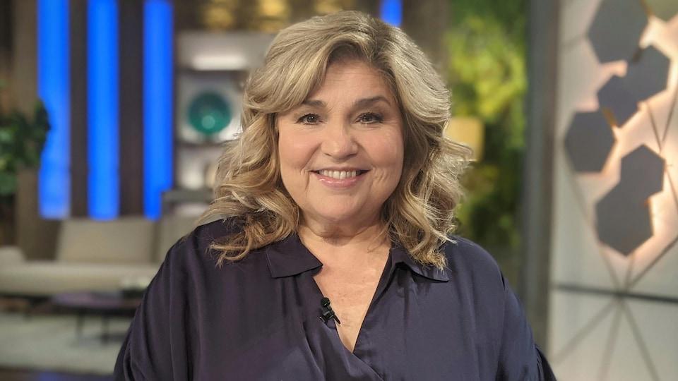 Une femme blonde, debout dans un décor de télévision, porte une chemise noire et sourit.