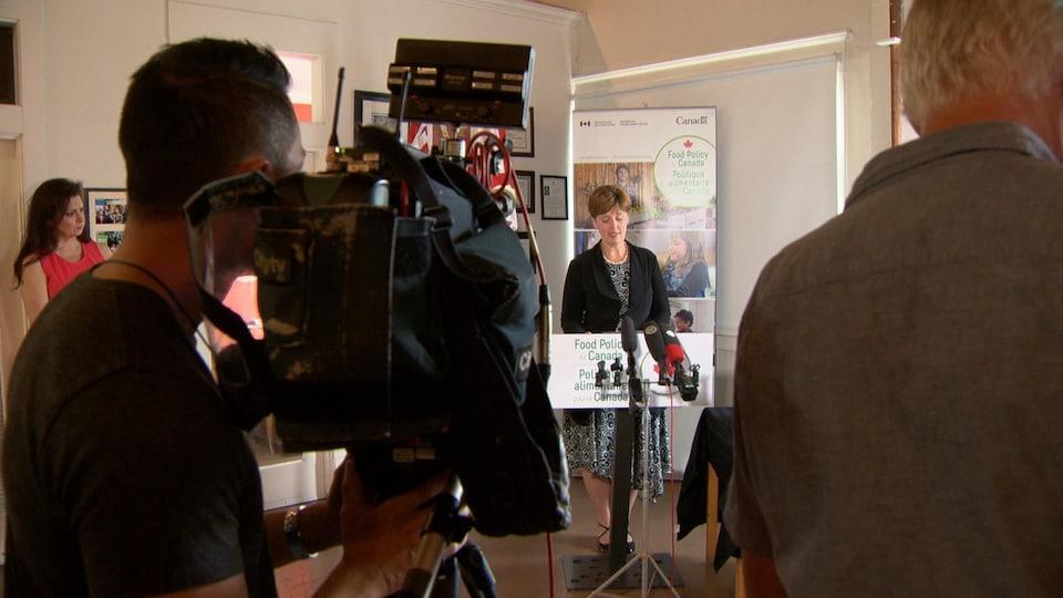 Une dame au podium devant des caméras.