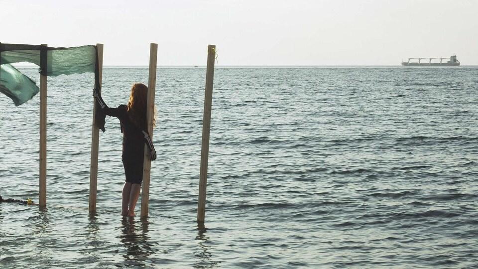 Une femme se tient sur une structure dans la mer, laissant penser qu'elle marche sur l'eau.