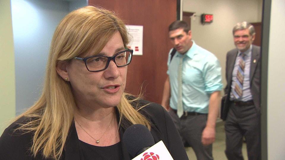 Marie-Claude Rioux en entrevue alors que des personnes assistant à la réunion du comité quittent la salle.