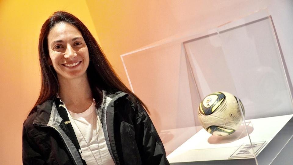 Marie-Ève Nault au Musée Pop, à côté d'un ballon de soccer recouvert d'un cube de verre.