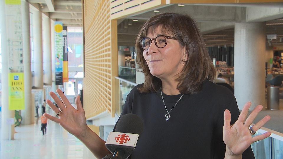 Elle parle au micro de Radio-Canada au deuxième étage de la Grande Bibliothèque.