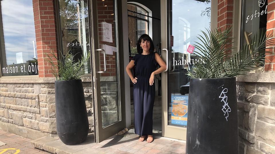 Marie-Josée Fernandes pose pour la caméra dans le cadre de porte de sa boutique.