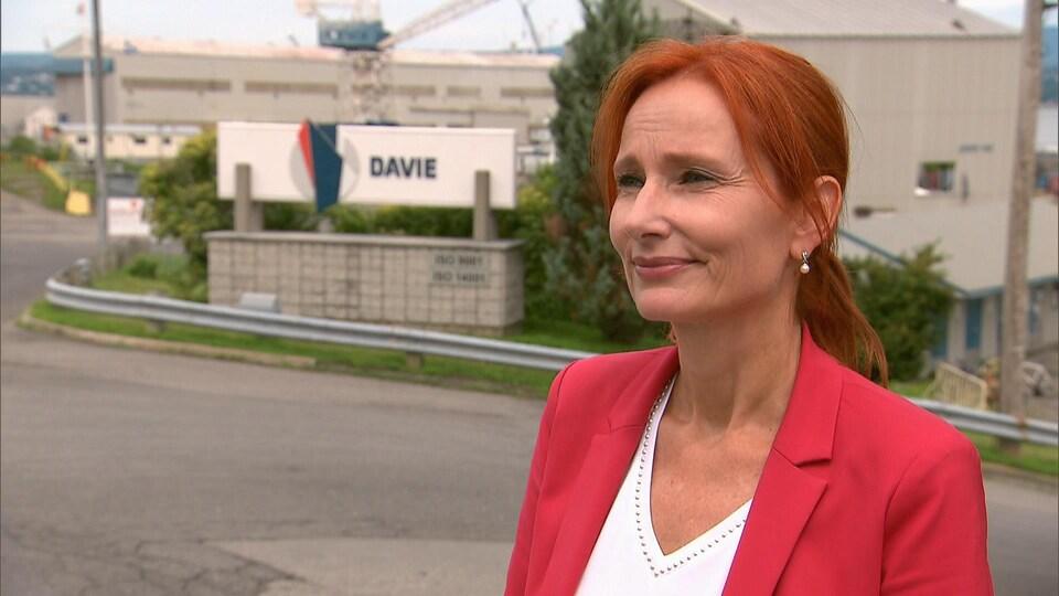 Marie-Josée Morency en entrevue, à l'extérieur, devant l'entrée du Chantier Davie. Elle porte un veston rouge. Elle a un regard fier.
