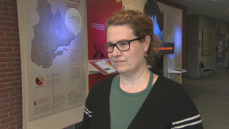 Une femme se trouvant dans le corridor d'un établissement d'enseignement répond aux questions d'une journaliste.