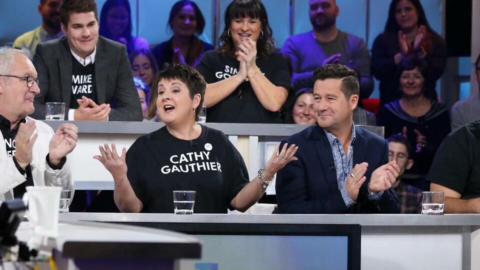Une femme s'exprime entourée d'hommes sur le plateau de l'émission Tout le monde en parle