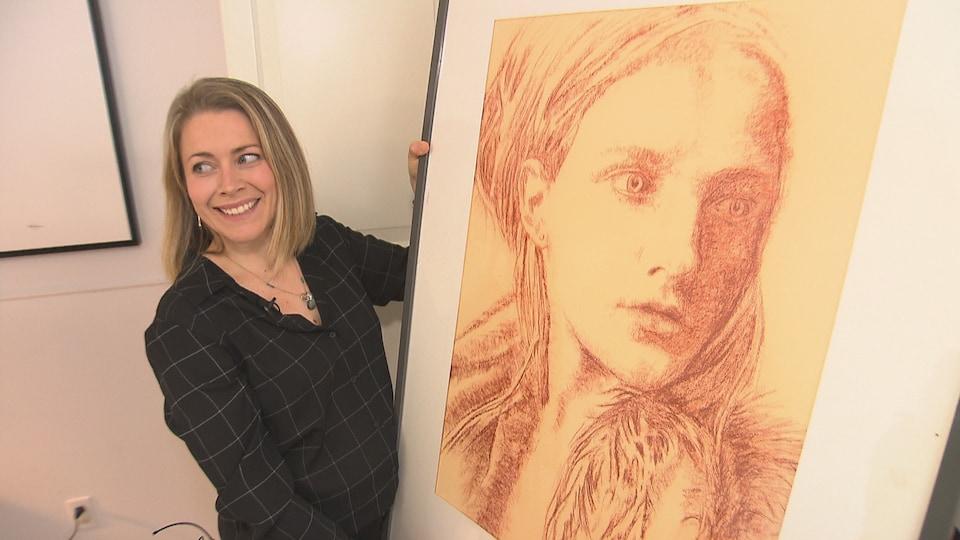 Marie-Michèle Desmarais tient une ilustration représentant une femme.