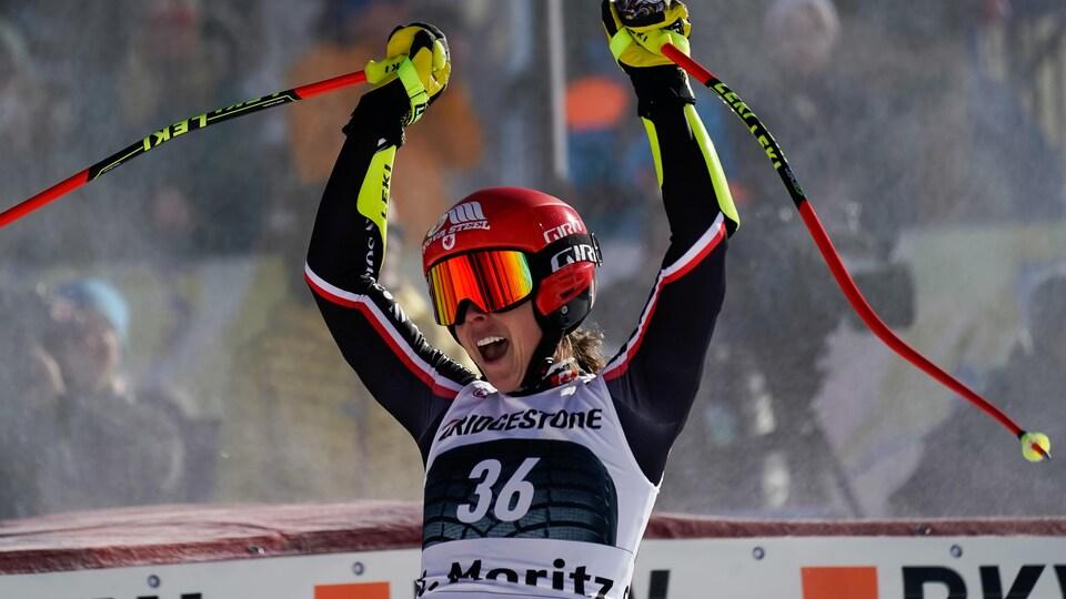 Portant ses lunettes et son casque, la skieuse Marie-Michèle Gagnon lève les bras pour célébrer après sa descente.