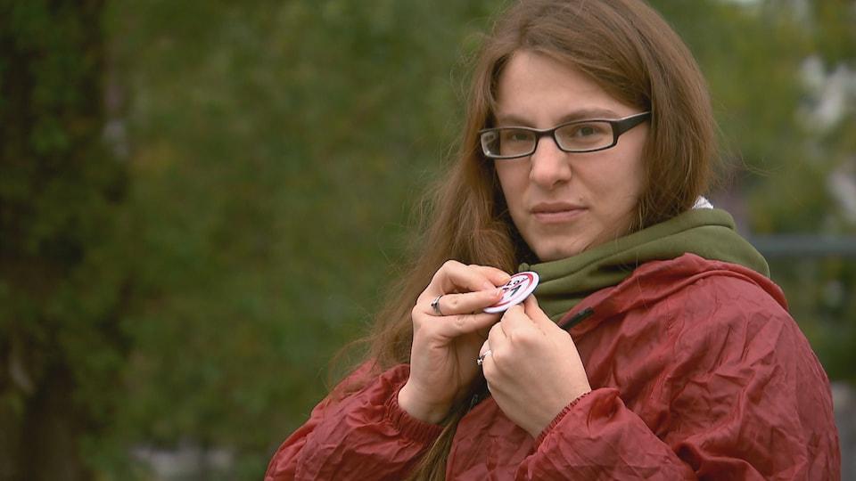 Marie-Pier Roussel épingle un macaron sur son chandail pour afficher son opposition à la loi 21.