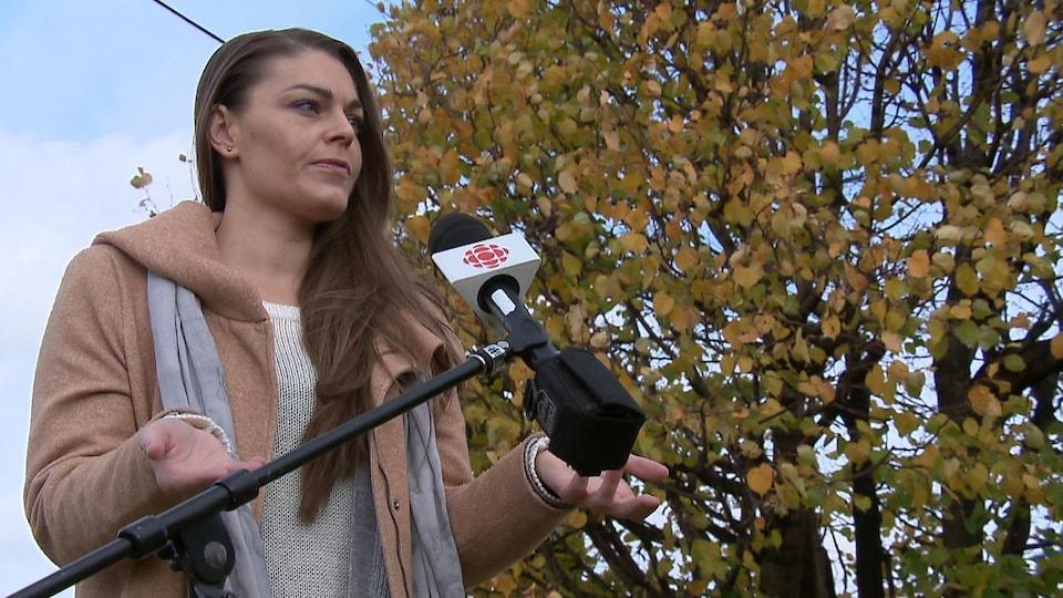 Marie-Renée Baillargeon devant un micro, à l'extérieur, le jour, l'automne.