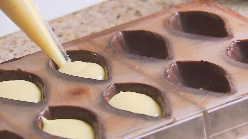 On voit un moule avec une première couche de chocolat. Une préparation au fromage est en train d'être insérée dans les moules.