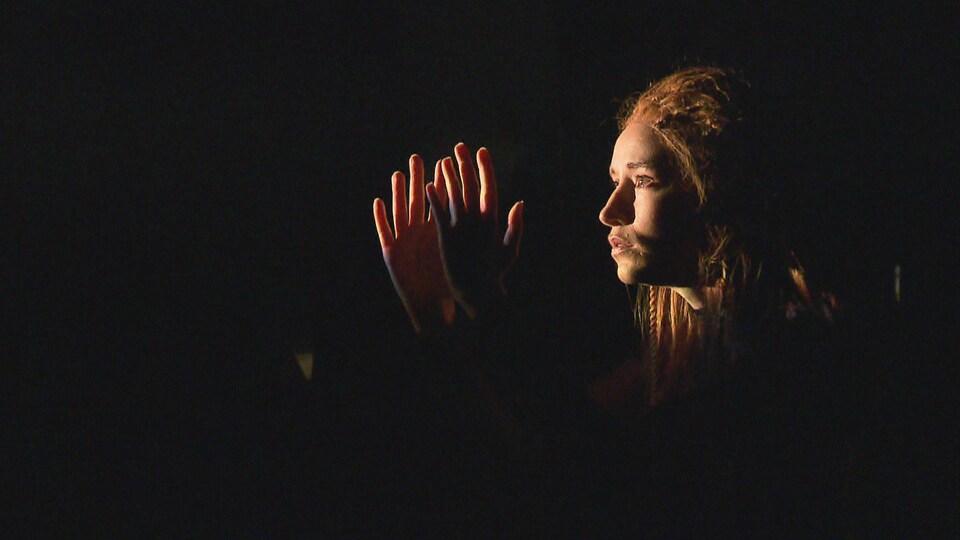 Une femme de côté, regarde ses deux mains qui sont à la hauteur de son visage.