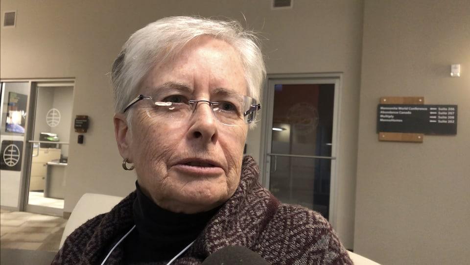 Une femme d'un certain âge parle au micro d'un journaliste.