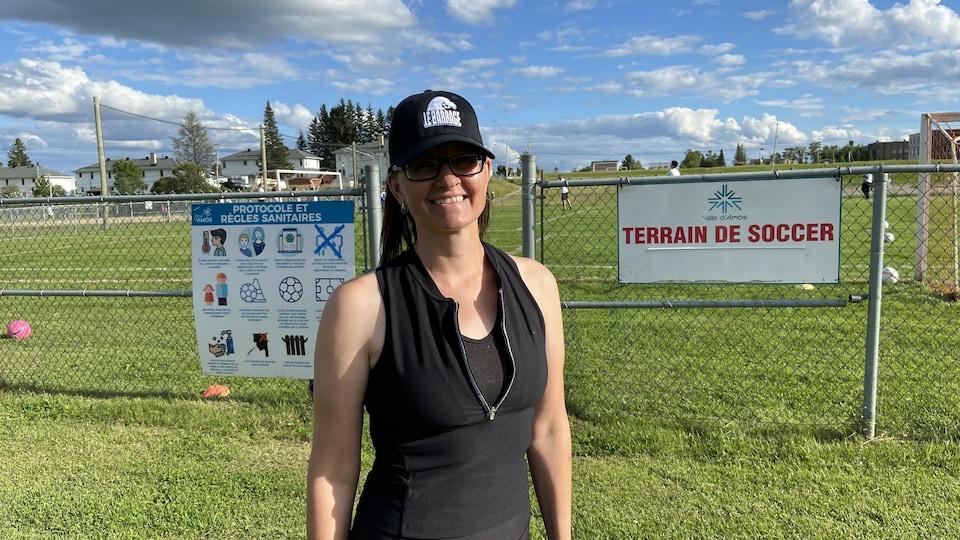 Marilyne Bouchard pose devant le terrain de soccer d'Amos.