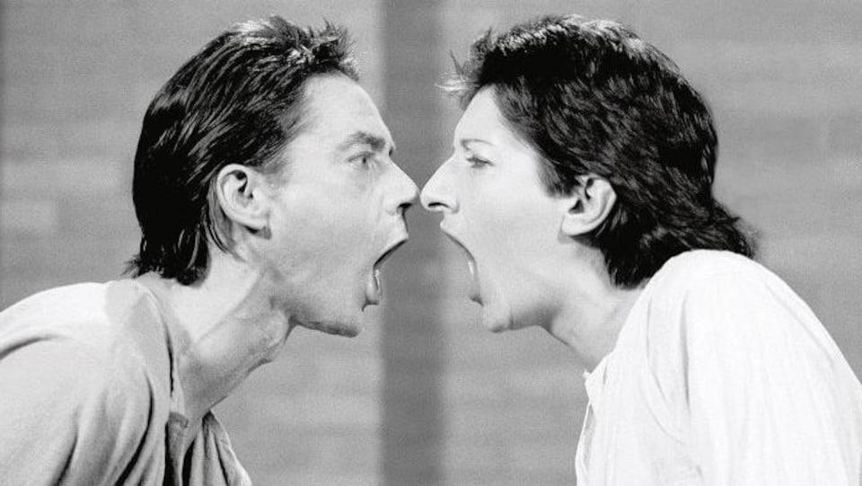 Ulay et Marina Abramović, face à face, bouches ouvertes.