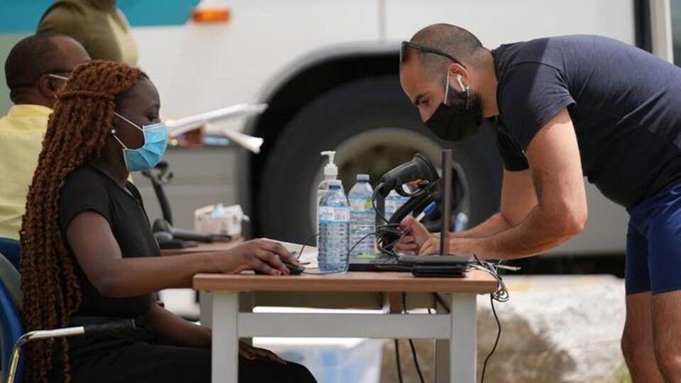 Un homme remplit un formulaire devant une personne oeuvrant auprès de l'équipe du Vaccibus.