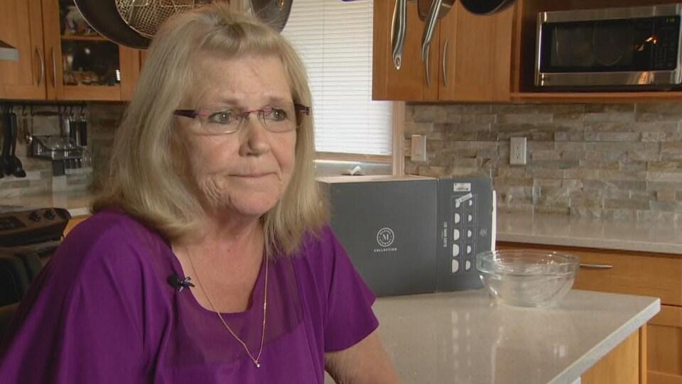 Une femme avec des lunettes dans une cuisine.