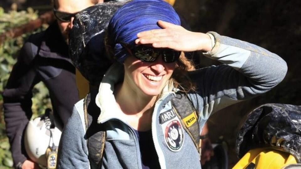 Une jeune femme souriante se cachant du soleil avec sa main.