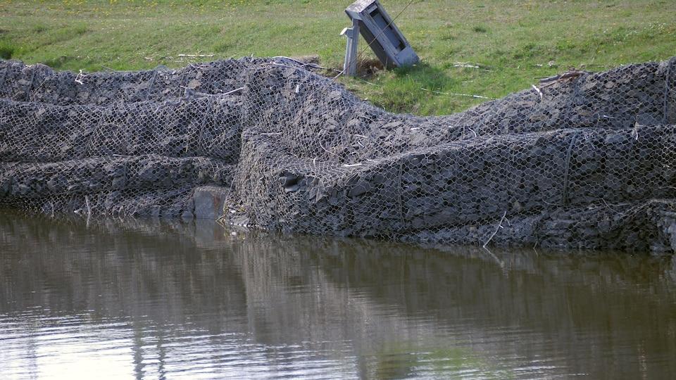 Un muret de pierre qui tombe dans l'eau.