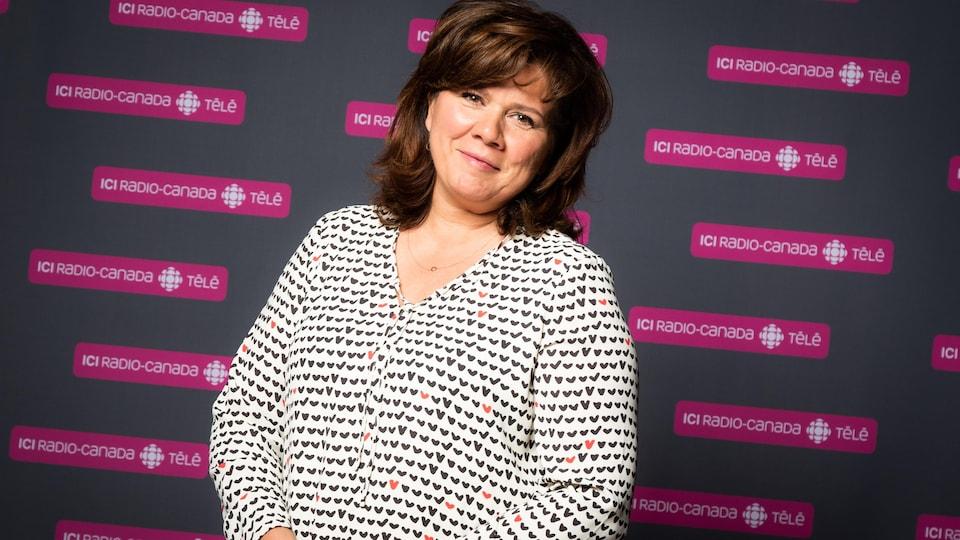 L'actrice et animatrice Marina Orsini prend la pose devant un mur rempli de logos d'ICI Radio-Canada Télé.