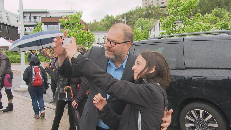 Un homme et une jeune femme se prennent en photo.