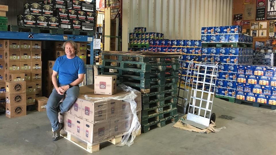 Dans son entrepôt de Matane, il est assis sur des boîtes de bières Auval. Derrière lui, de nombreuses boîtes de bière d'autres marques sont empilées.