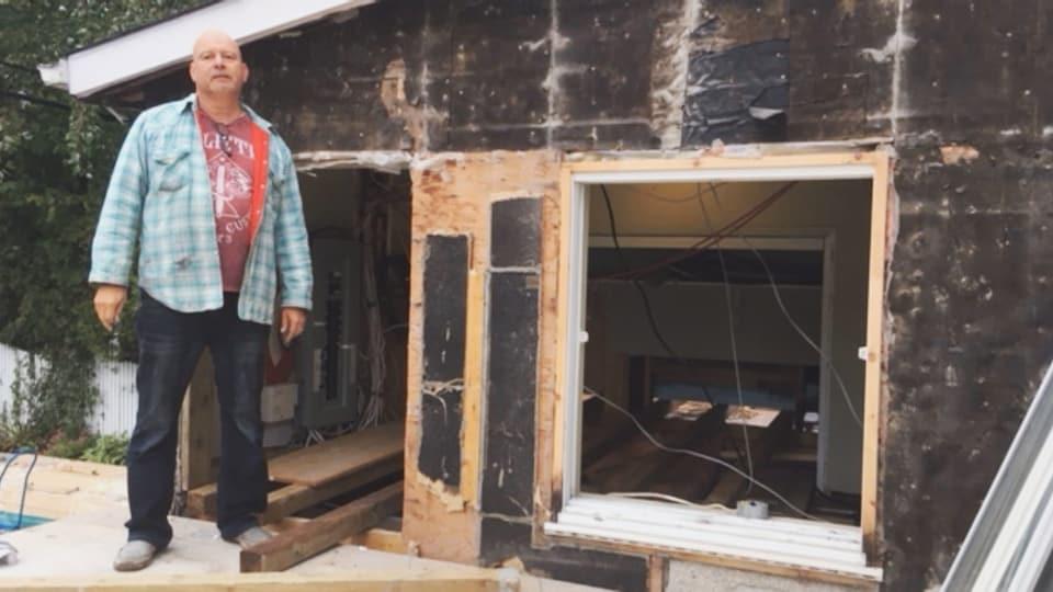Un homme se tient à côté d'une maison au plafond particulièrement bas.