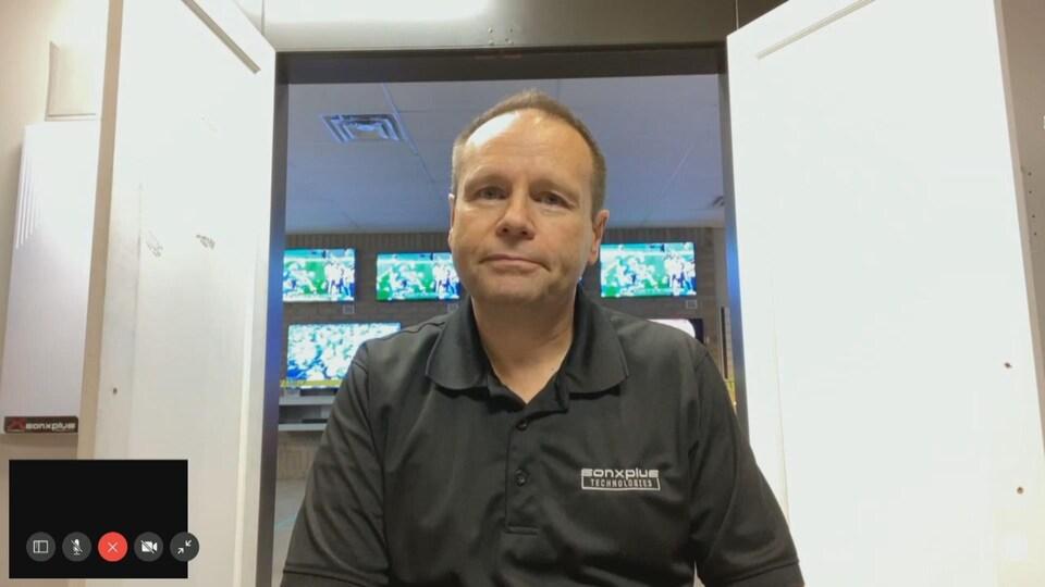 Une homme accorde une entrevue en visioconférence, en direct de son magasin de fournitures électroniques.