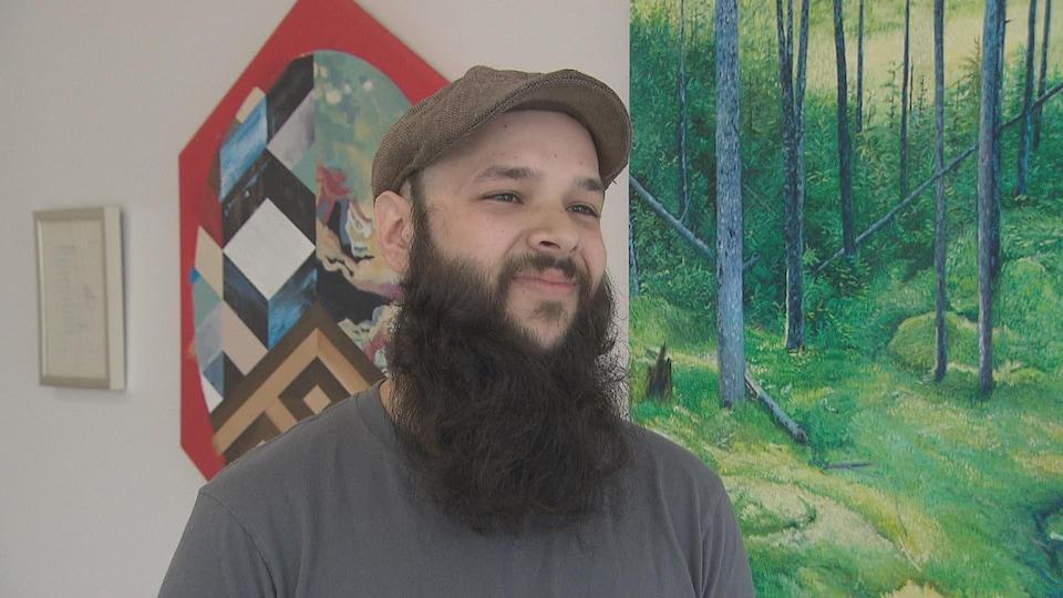 Un homme pose devant une peinture.